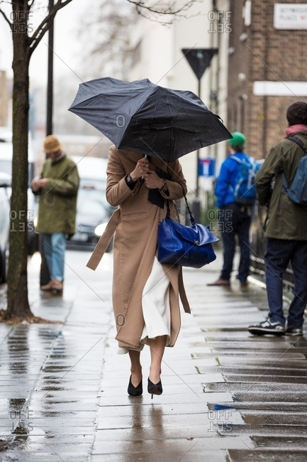 Woman holding large leather handbag and umbrella against the rain