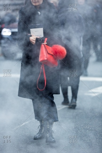 London, England - February 29, 2016: Woman walking through mist wearing all black carrying bright red handbag decorated with pom pom