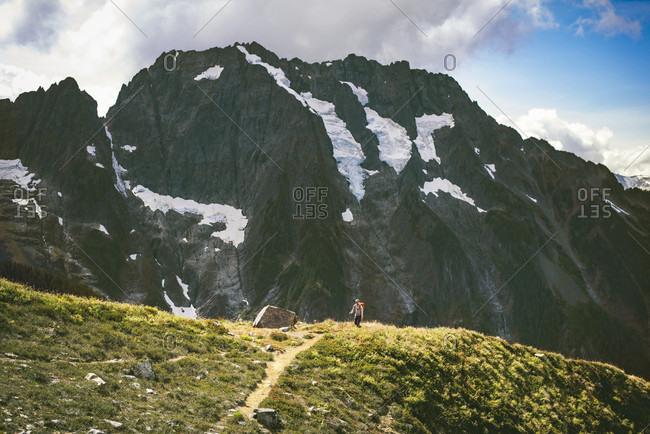 Backpacker hiking on trail towards Boston Basin in North Cascades National Park, Washington State, USA