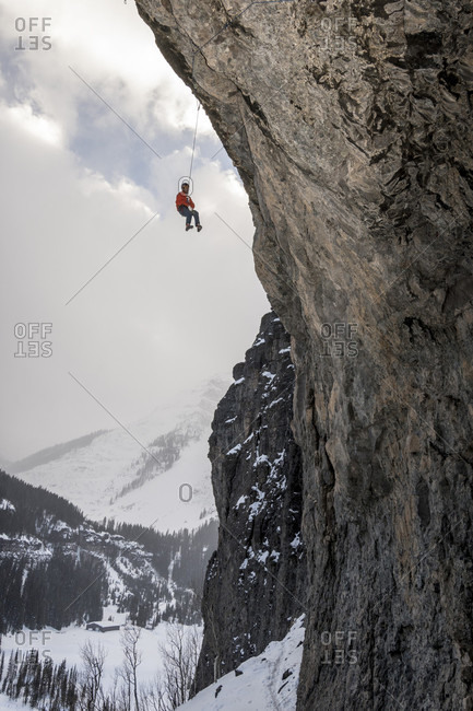 Side view of man descending from overhanging cave climb, Uncompahgre National Forest, Ouray, Colorado
