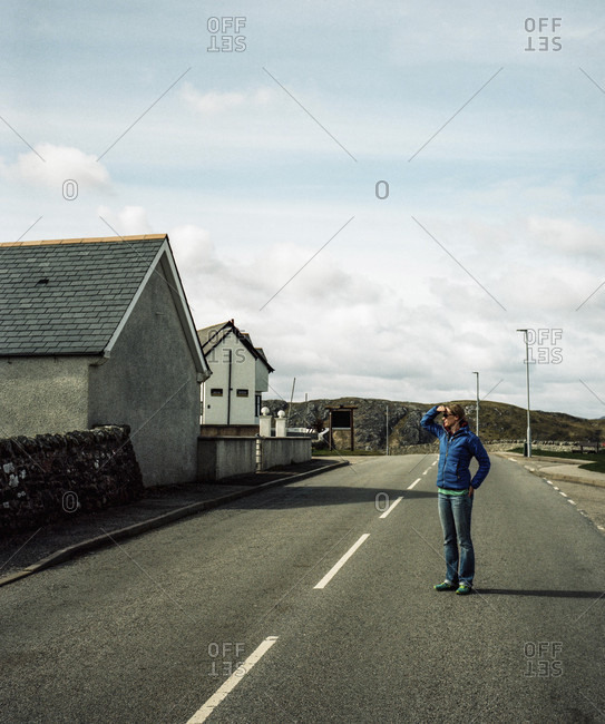 Woman standing on road in small town in northern Scotland, Bettyhill, Farr, Scotland, UK
