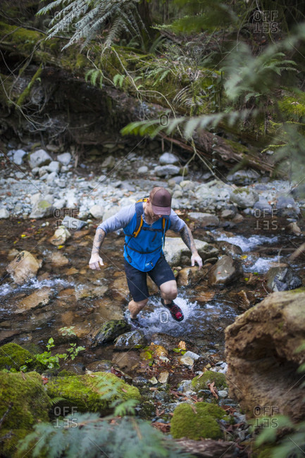 Man trail running across rocky stream near Elbow Lake in Fraser Valley, Harrison Mills, British Columbia, Canada