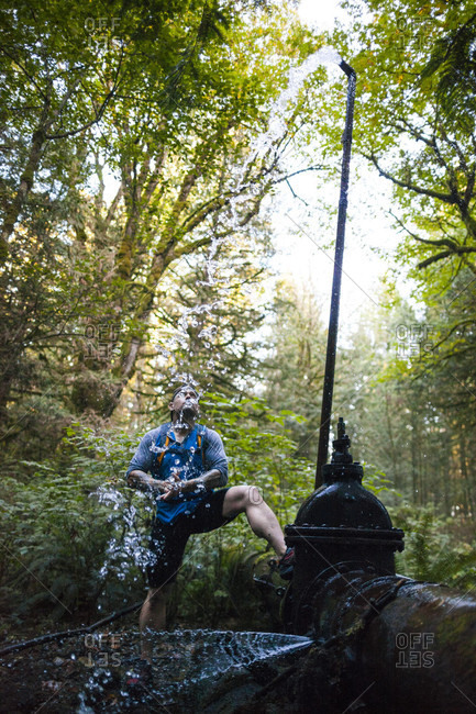 Man stops to drink water from fountain while trail running near Elbow Lake in Fraser Valley, Harrison Mills, British Columbia, Canada