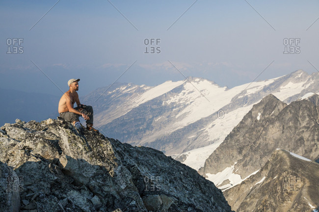 Mountain climber sitting at summit of Ashlu Mountain in Coast Mountain Range, Squamish, British Columbia, Canada