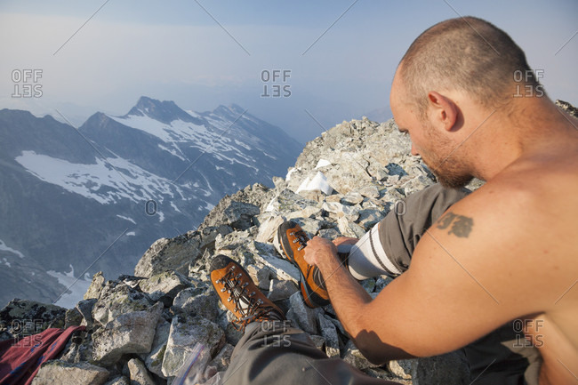 Mountain climber resting after reaching top of Ashlu Mountain in Coast Mountain Range, Squamish, British Columbia, Canada