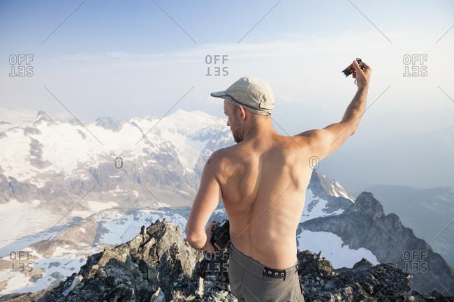 Mountain climber taking photo from summit of Ashlu Mountain in Coast Mountain Range, Squamish, British Columbia, Canada
