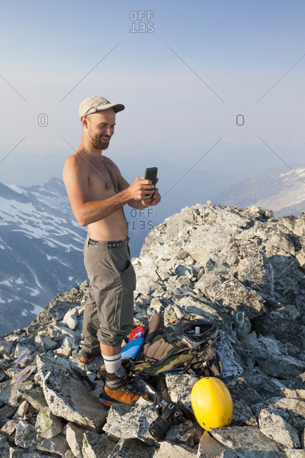 Mountain climber using smartphone at summit of Ashlu Mountain in Coast Mountain Range, Squamish, British Columbia, Canada
