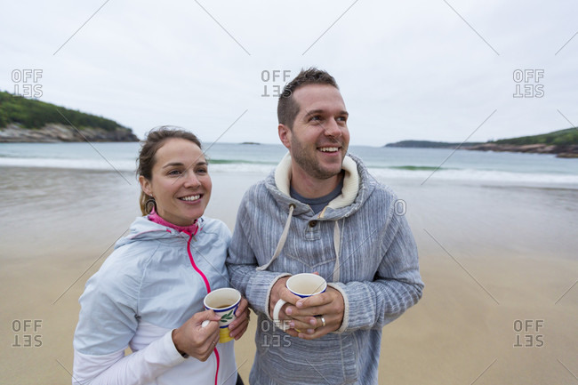 Couple drinking coffee on cloudy morning at Sand Beach in Acadia National Park, Maine, USA