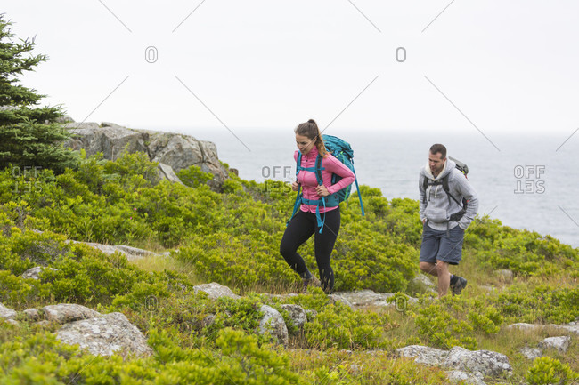 Man and woman walking on green cliffs during daytime, Acadia National Park, Maine, USA