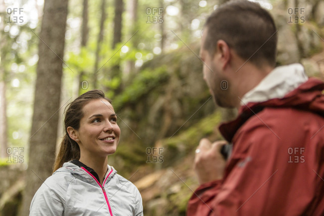 Couple smiling and talking in forest on Beach Mountain in Acadia National Park, Maine, USA
