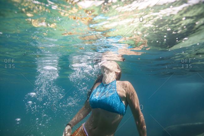 Woman surfacing underwater while swimming, Lake Tahoe, California, USA