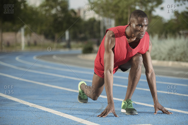 Male athlete preparing to run on all-weather running track, Barcelona, Spain