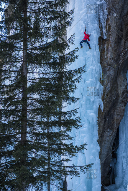 Two male climbers climbing ice falls in Ceresole Reale ice park, Piemonte, Italy