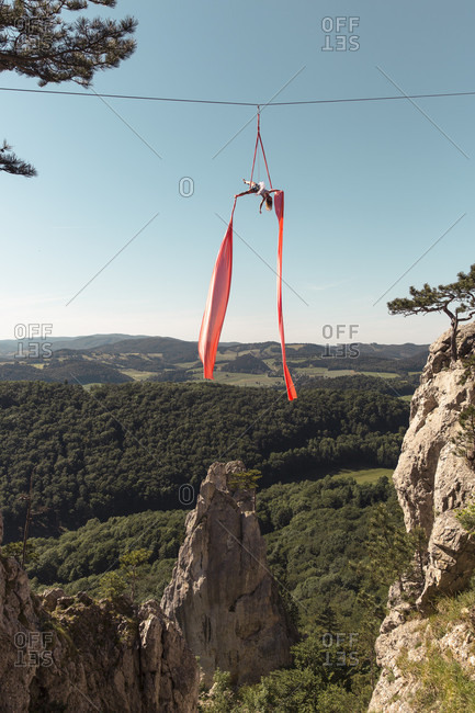 Female aerial silk gymnast performing over forested landscape 30 meters above ground, Lower Austria, Austria