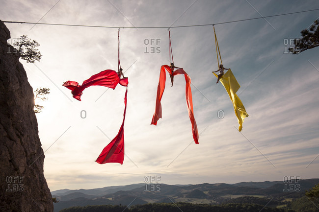 Female aerial silk gymnasts performing between two cliffs 30 meters above ground, Lower Austria, Austria
