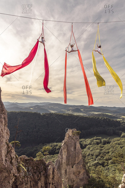 Female aerial silk gymnasts performing over forested landscape 30 meters above ground, Lower Austria, Austria