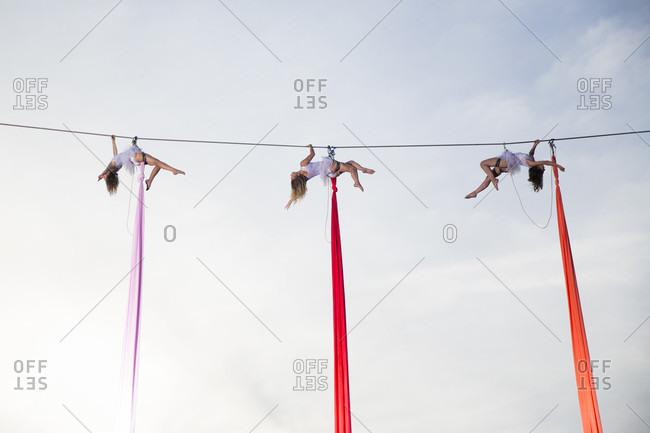 Female aerial silk gymnasts performing against sky 30 meters above ground, Lower Austria, Austria