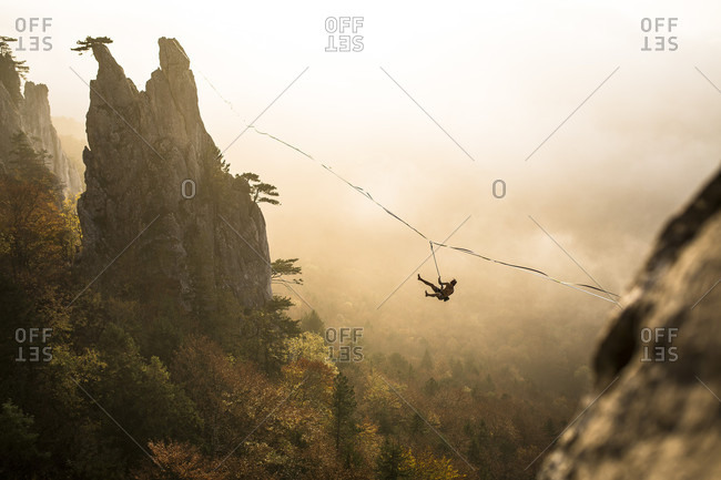Silhouette of man hanging from highline high above foggy forest, Lower Austria, Austria