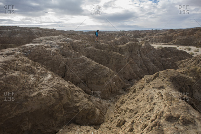 Woman hiking in barren badlands of Anza Borrego State Park, California, USA
