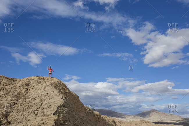 Woman standing on top of hill in badlands section of Anza Borrego State Park, California, USA