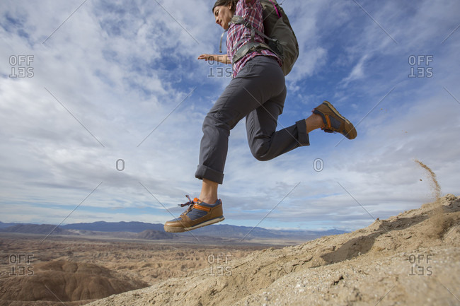 Adult woman jumping while hiking in badlands section of Anza Borrego State Park, California, USA