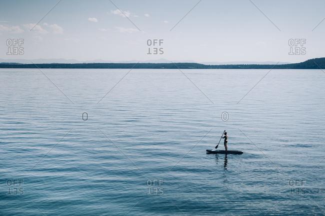 Woman standing up paddle boarder paddling on Flathead Lake, Montana, USA