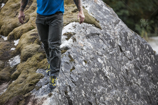 Man walking on crest of large boulder while bouldering near Elbow Lake in Fraser Valley, Harrison Mills, British Columbia, Canada