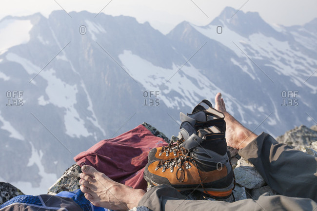 Hiker resting after reaching top of Ashlu Mountain in Coast Mountain Range, Squamish, British Columbia, Canada
