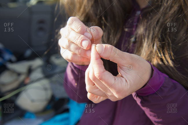 Close up of female anglers hands as she prepares her line for fishing in Colorado River, Silverthorne, Colorado, USA