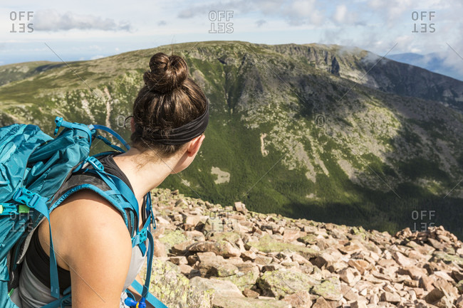 Teenage girl looking down at view while hiking at top of Cathedral Trail on Mount Katahdin in Baxter State Park, Maine, USA