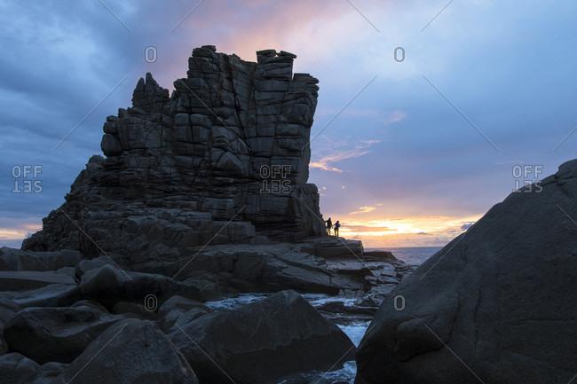Two people watching sunset by coastal rock formation, Sardinia, Sardinia, Italy