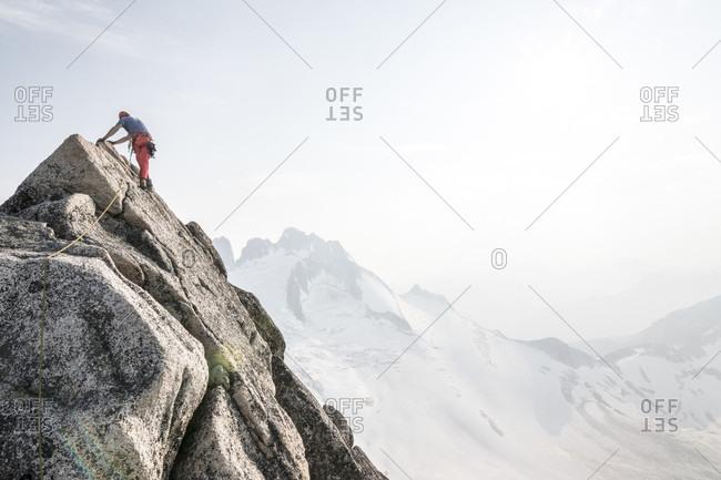 Mountain climber climbing up Bugaboo Spire, Bugaboo Mountains, British Columbia, Canada
