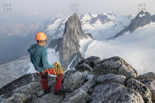Mountain climber looking down at view from Bugaboo Spire, Bugaboo Mountains, British Columbia, Canada
