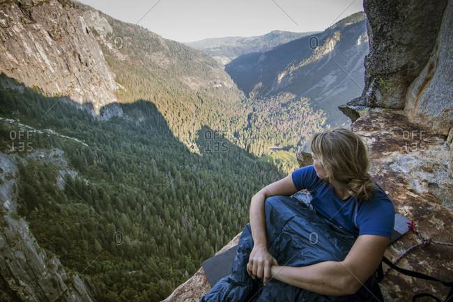 Woman sitting in sleeping bag on Dano Ledge, Yosemite Valley, Yosemite National Park, California, USA