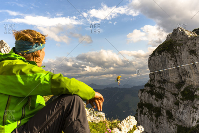 Man watching another highlining on tightrope in Lower Alps, Lower Austria, Austria