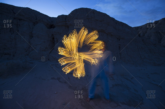 Woman creating simple light painting with flashlight light trails in Anza Borrego State Park at dusk, California, USA