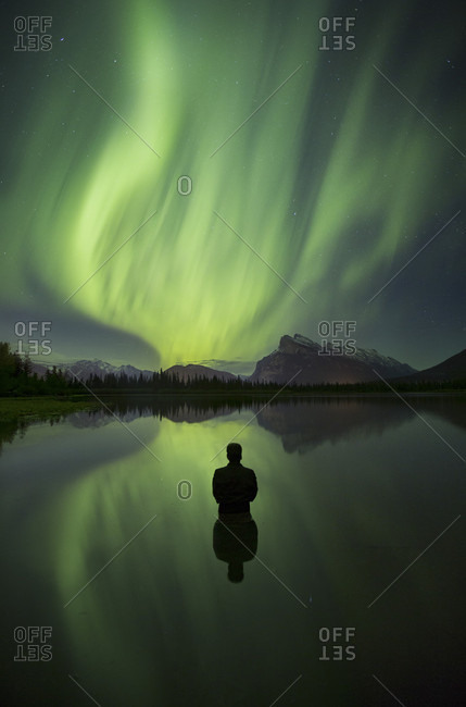 Aurora Borealis over person standing in lake and mountains in Banff National Park, Alberta, Canada