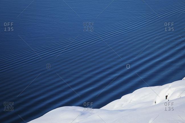 Ripples in water and snowy ocean coastline, Ilulissat, Greenland, Denmark