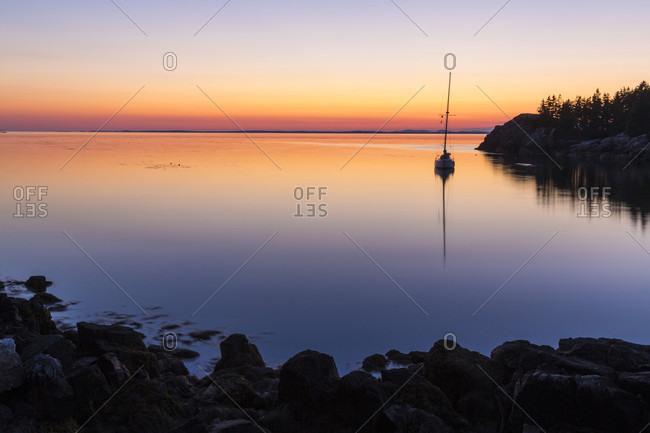 Sailboat at sunset moored in Duck Harbor, Isle au Haut, Acadia National Park, Maine, USA