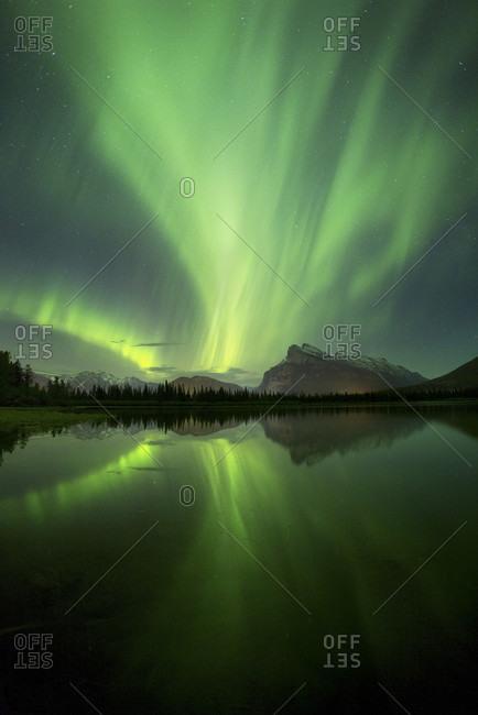 Aurora Borealis over lake and mountains in Banff National Park, Alberta, Canada