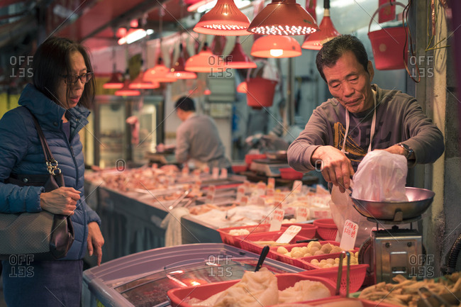 Hong Kong, People's Republic of China - March 18, 2018: Marketplace vendor weighing shopper's food items