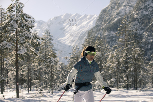 Woman skiing alone in snowy wilderness