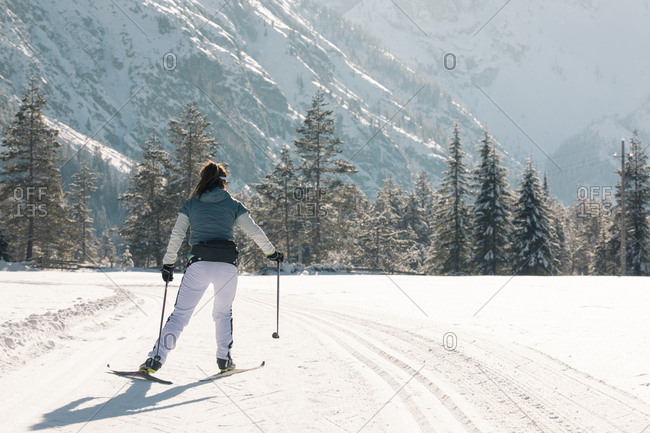 Back view of female skier practicing on sunny day