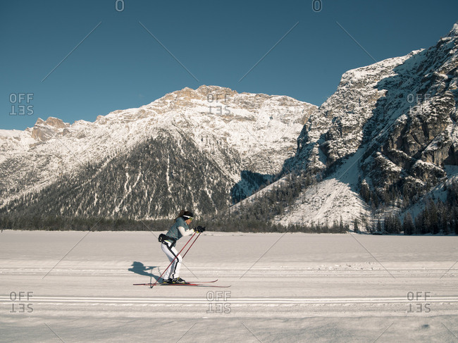 Side view of woman practicing skiing in flat snowy area