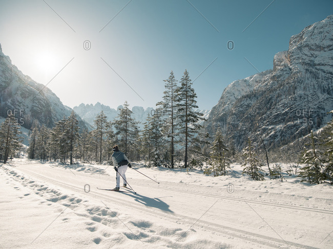 Skier practicing in front of sunny mountain skyline