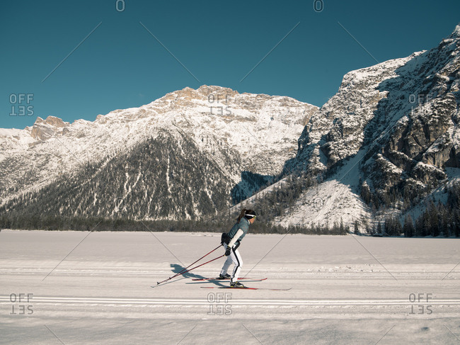 Skier on flat surface in front of snowy mountain range