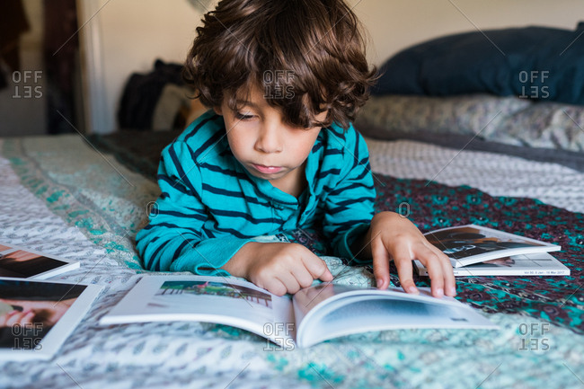 Young boy lying on bed reading books