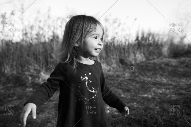 Portrait of little girl in field with impish smile on face