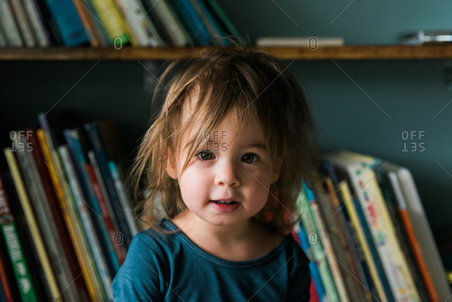 Portrait of little girl just after waking up in front of her book case