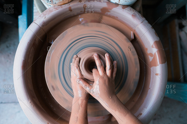 Overhead view of child's hands molding clay on a pottery wheel